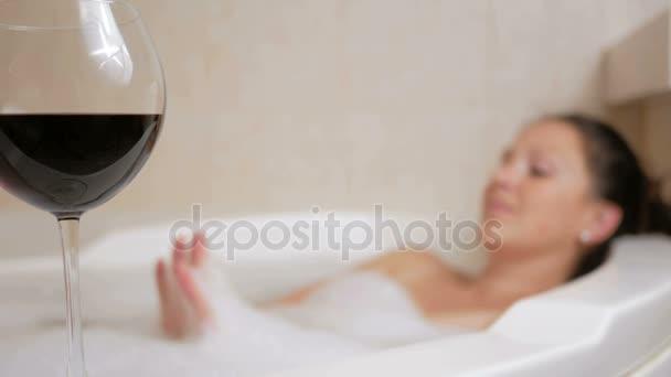 schönes Mädchen, das ein Schaumbad mit einem Glas Wein nimmt. ein großes weißes Bad und Freude auf seinem Gesicht. Entspannungskonzept