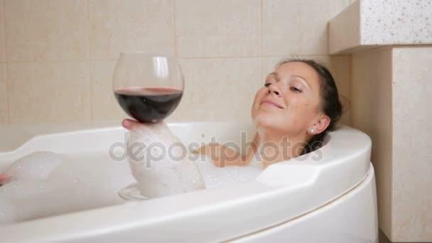 Krásná dívka si pěnovou koupel se sklenkou vína. Velká bílá vana a radost na tváři. relaxační koncept
