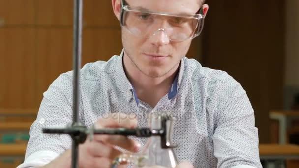 Mladý student muž pracující s chemikáliemi a zapisuje výsledky v univerzitě. Ochranné brýle a bez roucha. Kádinky a baňky s kapalinou