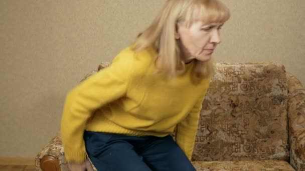 Women age can not climb off the couch because of the pain in the back in house. She sits back and makes a lumbar massage