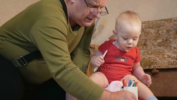 Atraktivní dětská sedí na banku a kresba se její dědeček značkami na papíře. Chlapec, močení a hrát si s rodinného domu. Dítě 1 rok