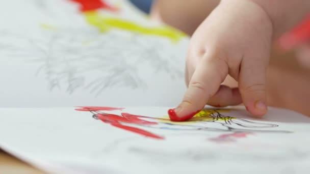 Hand das Kind zeichnet Farben auf Papier mit seiner Mutter. Der ...