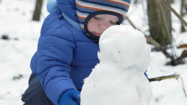 Portrait of an attractive toddler clinging snowman in the winter forest. Kid warm sport dressed in a blue jacket and dark pants, about a year