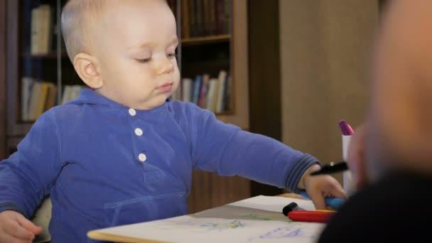 con su hijo Nieto dibuja marcadores sobre papel. El niño mira con ...