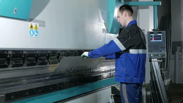 Člověk pracující s plechu na Cnc Lisy hydraulické brzdy. Vloží část a ohýbá do velké stroje v úhlu