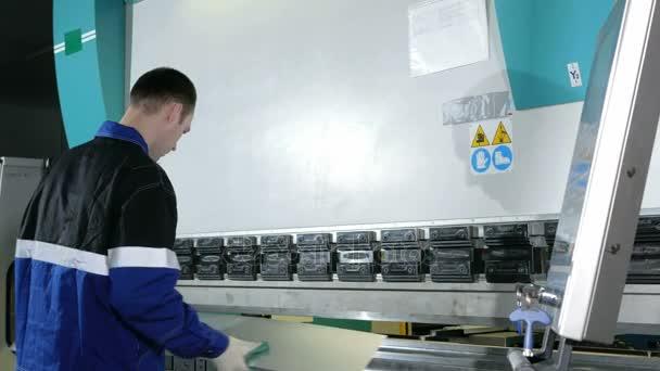 Inženýr v továrně řízené hydraulické stroj Cnc. muž pečlivě zadá data pro výrobu dílů