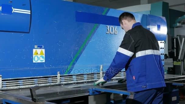 Muž řezání plechů ve velké Hydraulické tabulové nůžky. Práce v továrně dělá několik kusů dílů