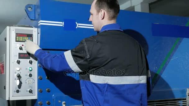 Člověk přizpůsobí provoz stroje pro dělení plechů na velké Hydraulické tabulové nůžky. Stiskne tlačítko a spustí výrobu dílů žehlení