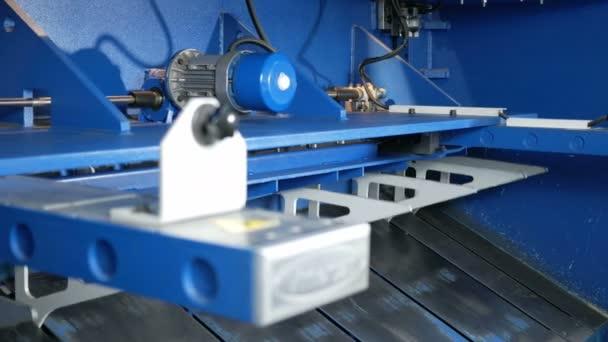 Stroj pro řezání plechů. Velké Hydraulické tabulové nůžky. Pohled zezadu: mnoho pohyblivých částí