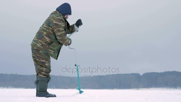 zimní rybaření na řece. muž vrtáky do ledu díru