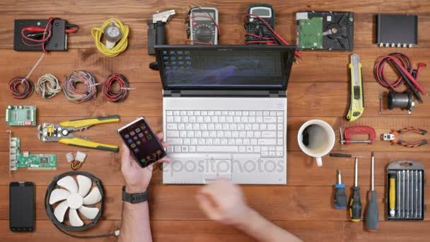 Ember szoftver mérnök dolgozik a pultnál egy telefon, egy laptop és egy csésze kávét. Nézd meg fából készült asztallap. Az üzenetet ellenőrzi, és úgy néz ki, Fénykép