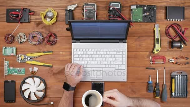 Ember szoftver mérnök dolgozik a pultnál, egy laptop és egy csésze kávét. Nézd meg fából készült asztallap. A kódot a billentyűzeten, és ivott egy forró ital nyomtat