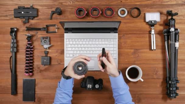 Objektiv fotoaparátu mužské fotograf odstraněn pro čištění rukou. Dřevěný stůl horní pohled. Zařízení pro střelbu na stůl