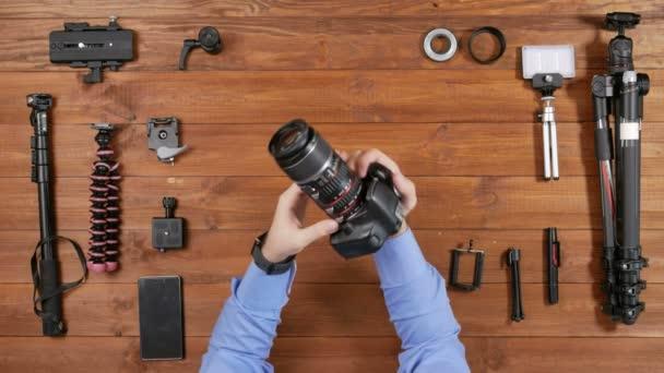 Fotografo maschio prende un obiettivo macro e un anello supplementare dalla fotocamera. Vedi piano di tavolo in legno. Attrezzatura per il tiro sul tavolo