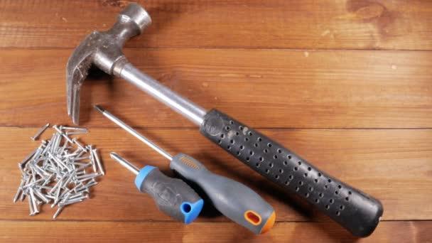 Nástroje pro tesaře leží na dřevěný stůl. Kladiva, šroubováky, hřebíky. Koncepce práce s dřevem
