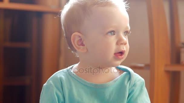 Atraktivní kluk 2 roky hraje doma s plastovou kachna. Dítě mluví ke svým rodičům. Detail