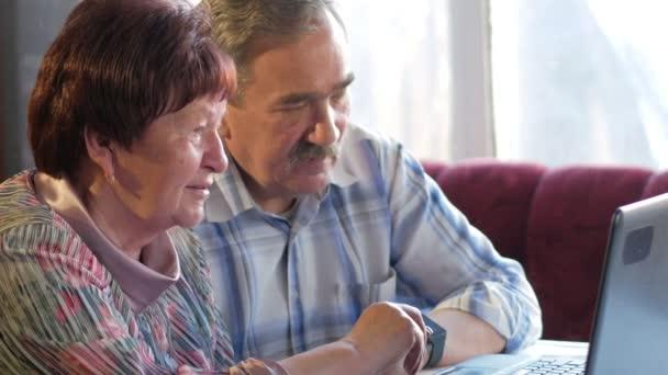 Starší pár sedí doma u notebooku. Žena čte zprávy, muž s knírkem sedí vedle něj a rozhovory