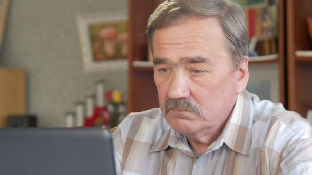 Ein älterer Mann mit Schnurrbart sitzt hinter einem Laptop und löst Probleme. er blickt ernst auf den Monitor