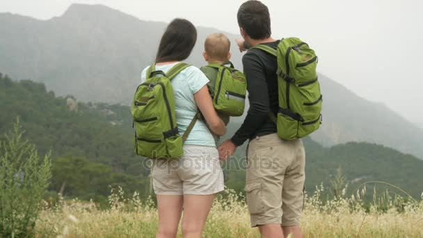 A young family of travelers with a baby looking back at the mountains. Everyone has the same green backpacks.