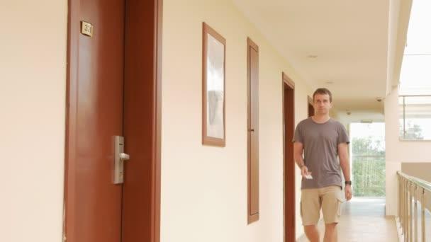 Ein Mann öffnet ein Hotelzimmer mit einem Kartenschlüssel.