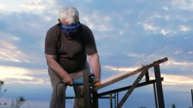 A man in age cuts off a metal angle grinder at sunset. Beautiful sky behind the worker