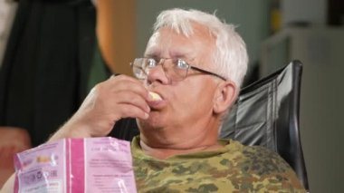 Senior man eating corn sticks and watching TV. Sits in a leather armchair with glasses