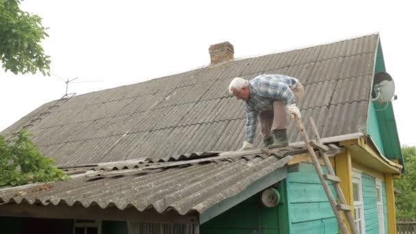 Starší muž je oprava střechy, sám. Starý dřevěný dům v břidlice
