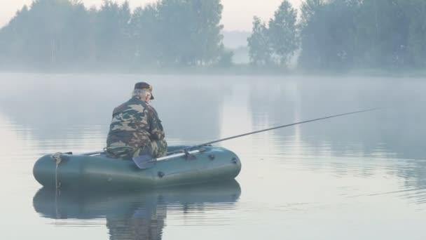 Nafukovací člun s mužské rybář na jezeře v mlze. Brzy ráno.