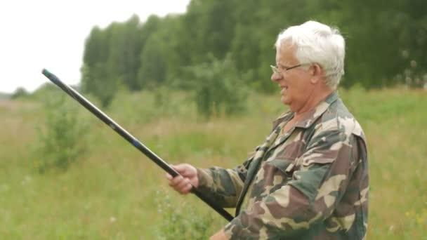 Пожилой мужчина Рыбалка на речке летом. Использует удочку и червей ...