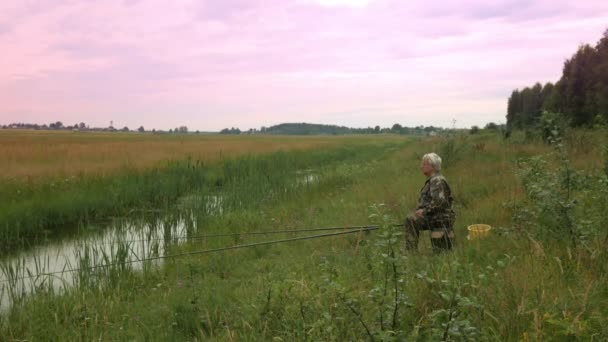Starší muž je lov na malé řece v létě. Využívá rybářský prut a červy. Les a vysoké zelené trávy