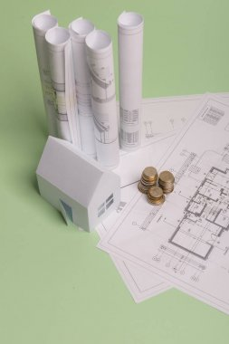 White family paper house , stack of money coins, house projects plan and blueprints on mint background paper. Minimalistic and simple concept, style. Vertical orientation.