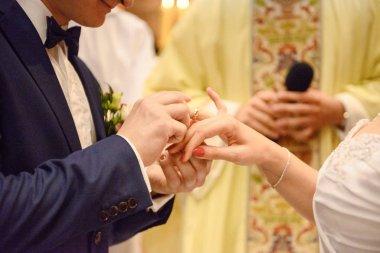 the bride and groom during the wedding ceremony put wedding ring