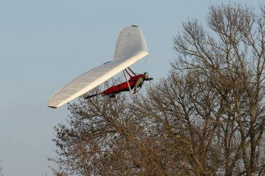 Hang glider pilot makes maneuvers close to the trees