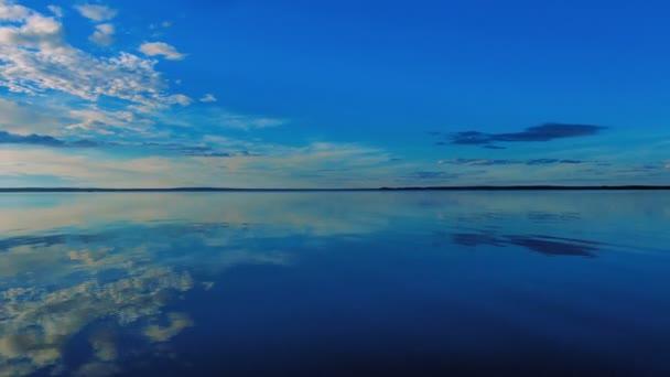 Obloha s mraky odrážející v klidné vodě