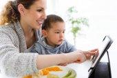 Fényképek Fiatal anya és a fia segítségével digitális tabletta, miközben eszik gyümölcsöt