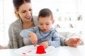 Krásná mladá matka a její syn jíst jahody želé na ho