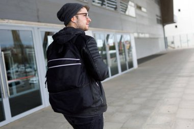 Modern young man listening to music with earphones in the street