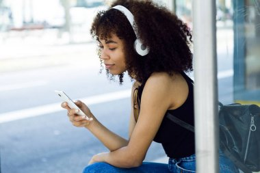 Beautiful young woman listening to music in city.