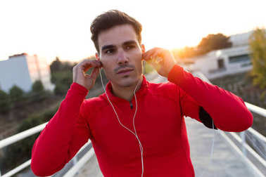 Sporty young man listening to music in the street.