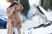 Fényképek A mobiltelefon használata a gyönyörű fiatal nő kéri segítségnyújtás-autó