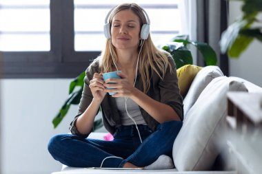 Pretty young woman listening to music with headphones while drinking cup of coffee on sofa at home.