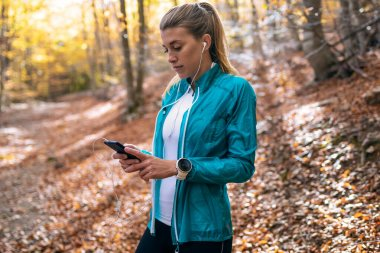 Sporty young woman using her mobile phone while relaxing after running in the park in the autumn morning.