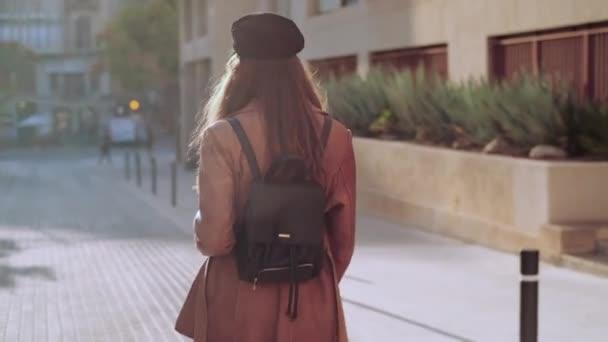Videó csinos fiatal nő néz kamera, miközben sétál az utcán.