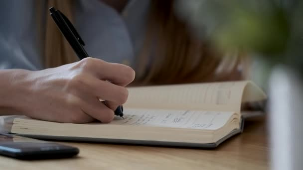 Close-up of a woman's hand writing in her agenda in the office.