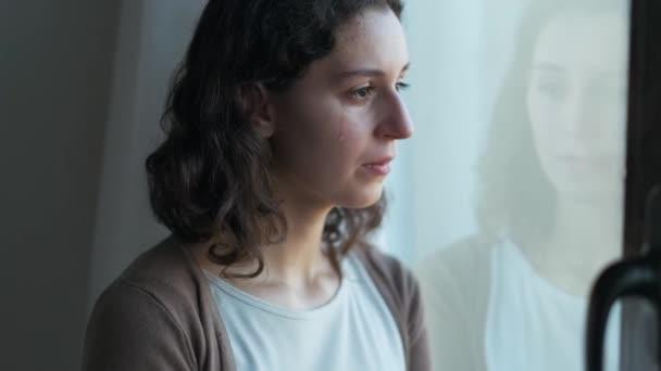 Videó szomorú fiatal nő sír, miközben néz ki az ablakon otthon.