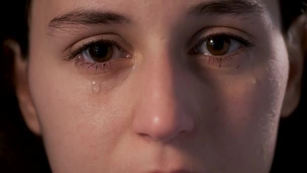 Video mladé ženy, jak pláče na černém pozadí. Myšlenka duševní choroby.