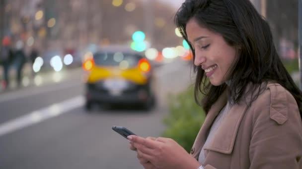 Video einer hübschen jungen Frau, die auf dem Handy SMS schreibt, während sie darauf wartet, nachts am Straßenrand abgeholt zu werden.