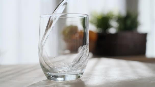 Video nalévání čerstvé čisté vody z láhve do sklenice na stole doma.