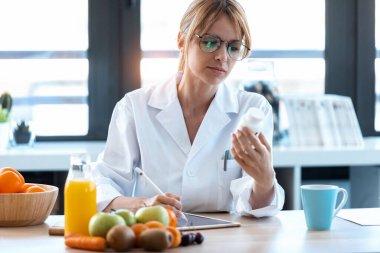 """Картина, постер, плакат, фотообои """"выстрел женщины диетолог врач выписывает медицинский рецепт на правильную диету на столе с фруктами, таблетками и добавками ."""", артикул 376989402"""