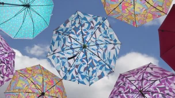 Bunte Regenschirme gegen blauen Himmel